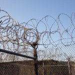 Concertina wire, a super sharp version of barbed wire, topped the fence surrounding the now defunct detention camp. The camp was originally used to hold troublesome refugees in the early 1990s and was repurposed in 2001 to hold detainees in support of the War on Terror.