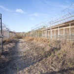 One of the gates at the abandoned Camp X-Ray is left open. The remnants of tire tracks still remain. The camp was originally used to hold troublesome refugees in the early 1990s and was repurposed in 2001 to hold detainees in support of the War on Terror.