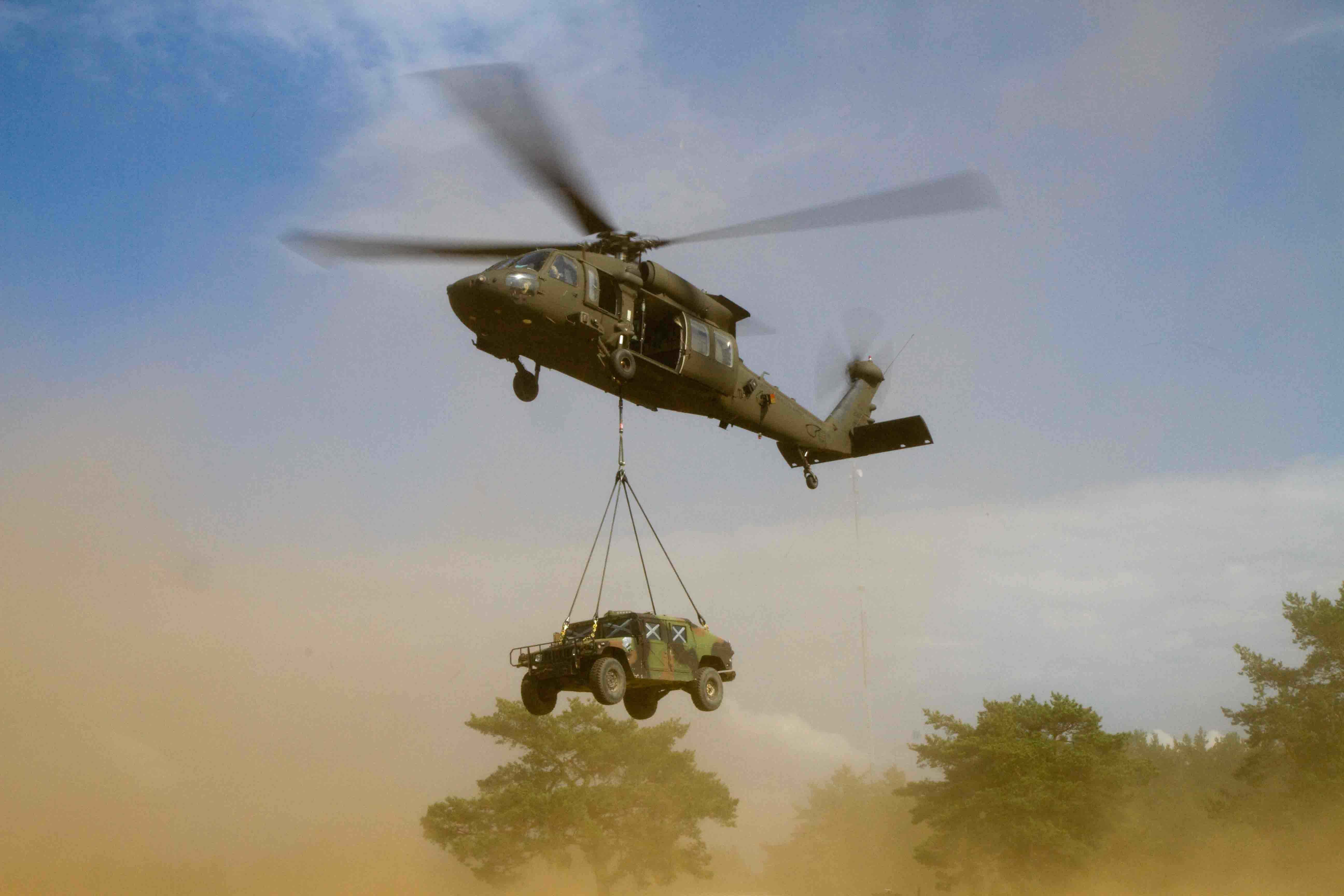 A UH-60M Black Hawk helicopter being operated by B Company, 43rd Assault Helicopter Battalion, 3rd Cavalry Regiment, 3rd Infantry Division, lifts off after having a High Mobility Multipurpose Wheeled Vehicles (HMMWV) sling loaded to it by Soldiers on the ground assigned to Dog Company, 1st Battalion, 503rd Infantry Regiment, 173rd Infantry Brigade Combat Team (Airborne), 4th Infantry Division and Lithuanian Land Forces Soldiers assigned to the Grand Duchess Birut? Uhlan Battalion (BUB), during exercise Uhlan Fury being held at the Gen. Silvestras Zlikaliskas Training Area, Pabrade, Lithuania, Aug. 10, 2015. The U.S. units are in Europe as part of Atlantic Resolve, a demonstration of continued U.S. commitment to the collective security of NATO and to enduring peace and stability in the region. U.S. Army Europe is leading Atlantic Resolve enhanced land force multinational training and security cooperation activities taking place across Estonia, Latvia, Lithuania, Romania, and Bulgaria to ensure multinational interoperability, strengthen relationships among allied militaries, contribute to regional stability and demonstrate U.S. commitment to NATO. (U.S. Army Photo by Sgt. James Avery, 16th Mobile Public Affairs Detachment)