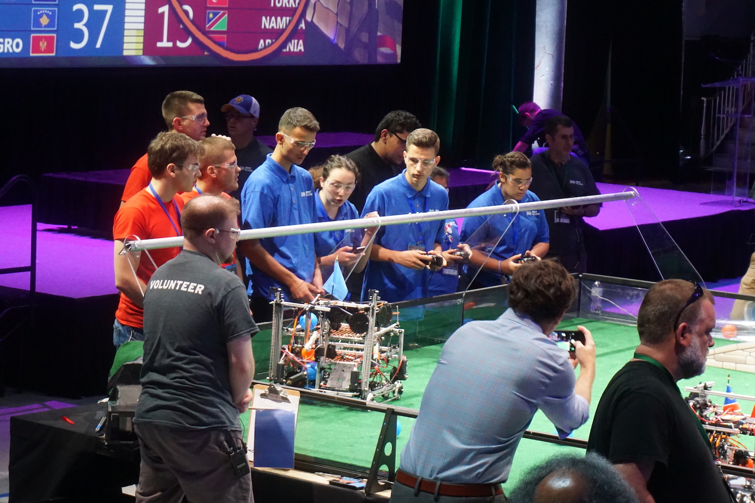 Two teams crowd around the arena as their robots battle to 'purify' the playing field of the beach-ball contaminants. (Ritu Prasad/Medill News Service)