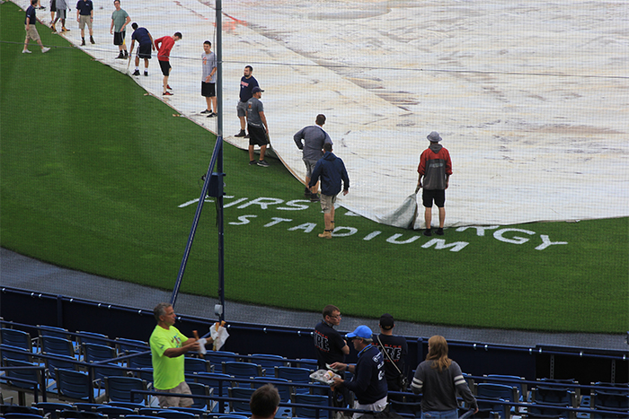 The grounds crew getting ready to take the tarp off the field.
